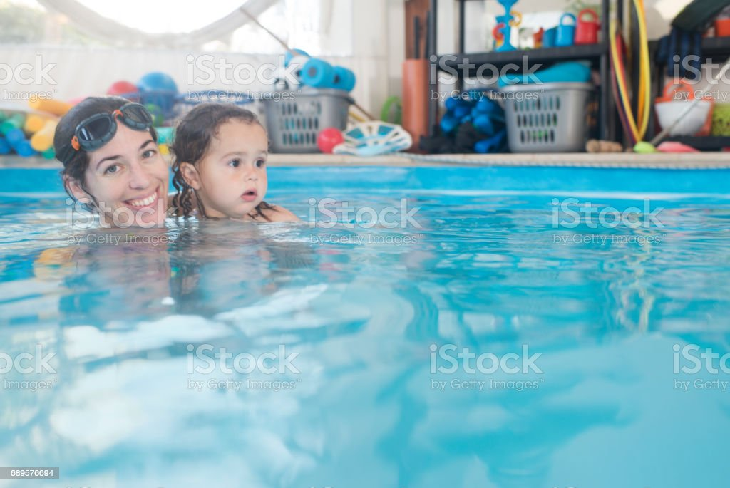 Portrait of swimming teacher with a learner baby at water pool.