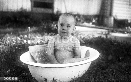 Baby taking bath outdoors in enameled dishpan on a hot summer day. Iowa, USA 1952. Scanned film with significant grain.