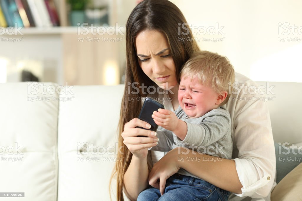 Baby tantrum fighting with his mother for a smart phone stock photo