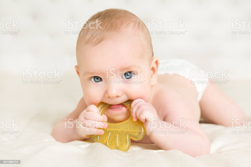 Baby Teether, Kid Bite Teething Toy in Mouth, Infant Child Growing First Tooth, Little Boy stock photo