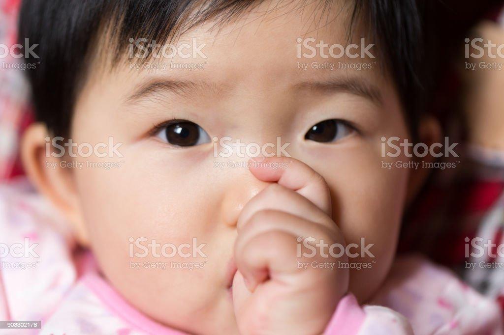 baby thumb sucking close-up stock photo