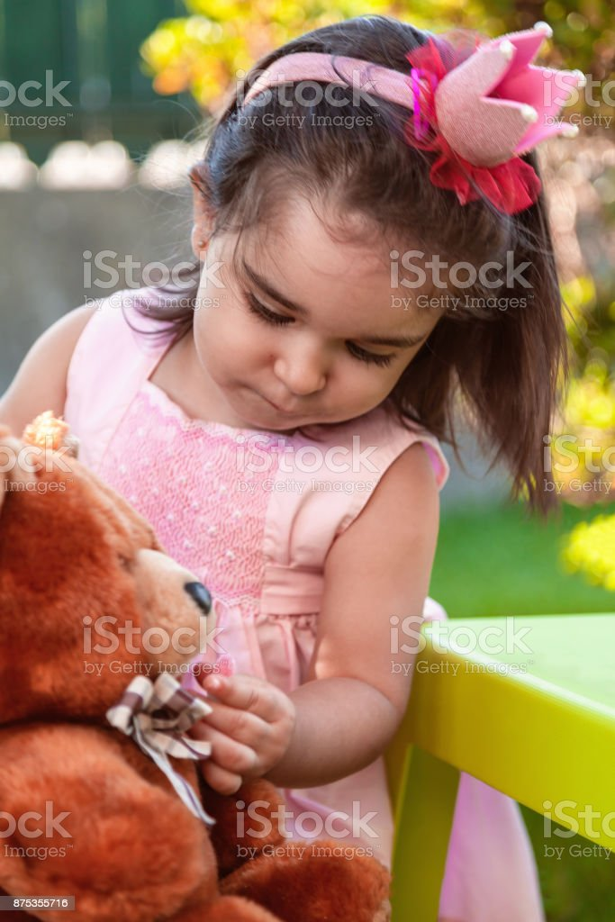 Baby toddler girl, playing in a tea party feeds best friend bff Teddy Bear with candy gummy. stock photo