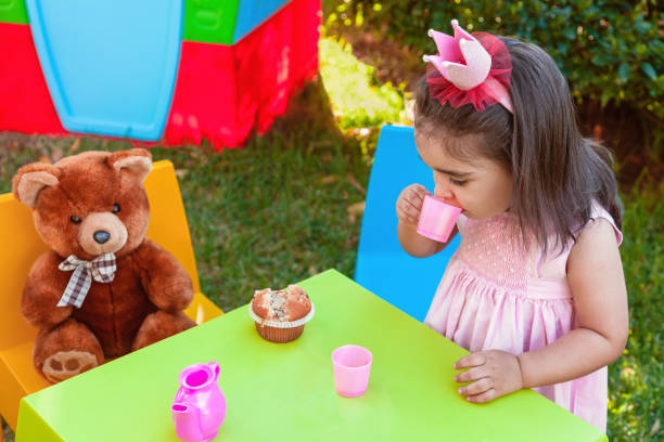 Baby toddler girl playing in outdoor tea party drinking from cup with best friend Teddy Bear sitting at table. stock photo