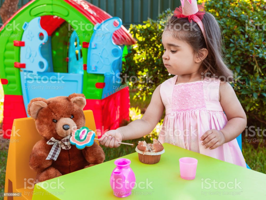 Baby toddler girl playing in outdoor tea party feeding her best friend bff Teddy Bear with a tasty lollipop. stock photo
