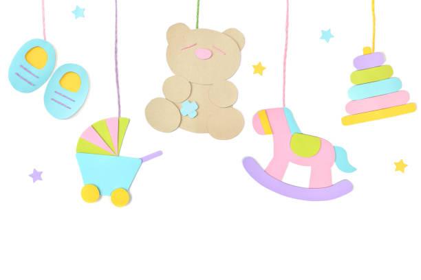 juguetes de bebé colgando papel cortado sobre fondo blanco - baby shower fotografías e imágenes de stock