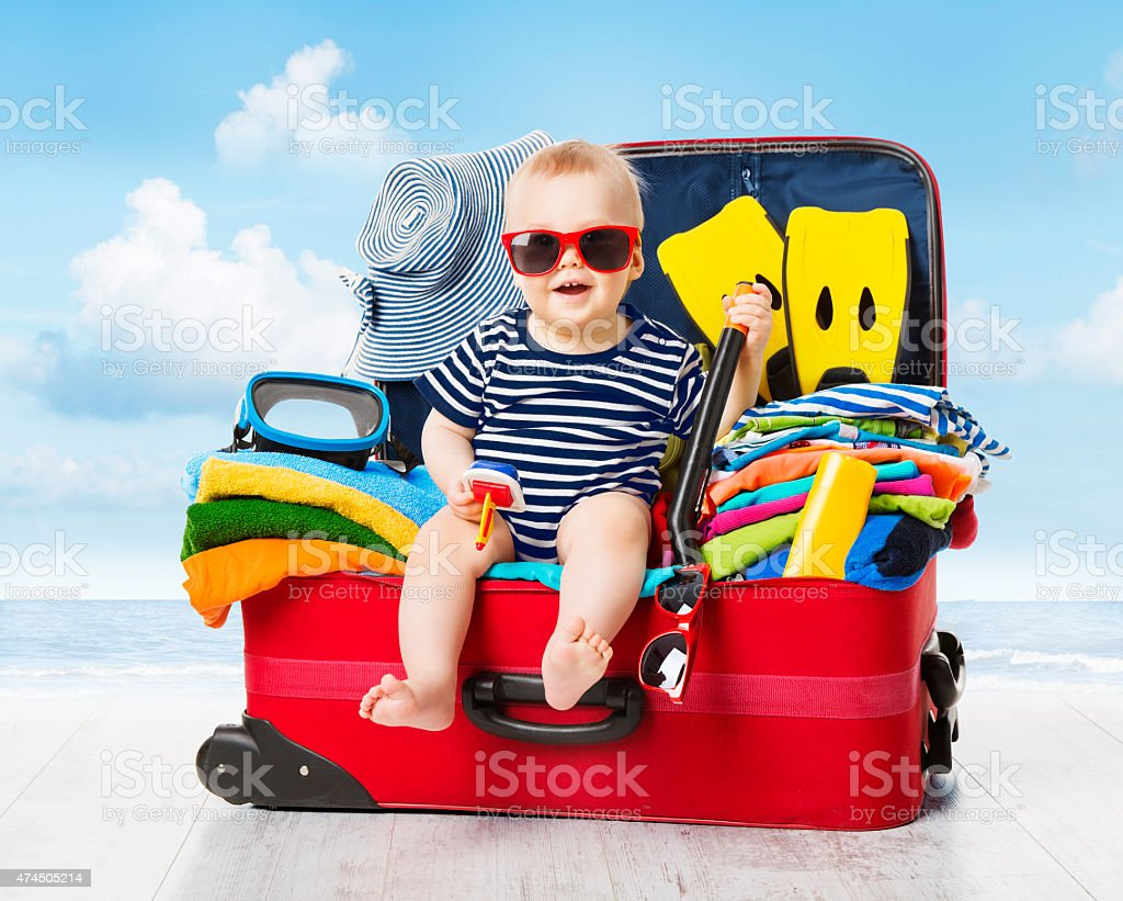 Baby Travel Suitcase. Kid Luggage Packed for Vacation Full Clothes Baby in Travel Suitcase. Kid inside Luggage Packed for Vacation Full of Clothes, Child and Family Trip 12-23 Months Stock Photo