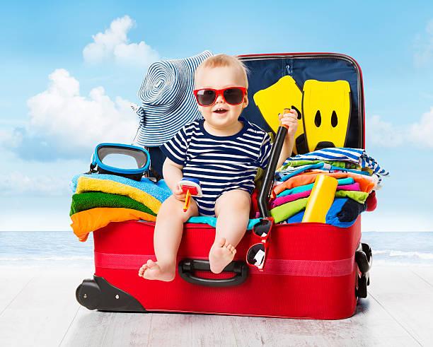 bébé dans la valise de voyage.   kid bagages une gamme complète de vêtements pour les vacances - valise humour photos et images de collection