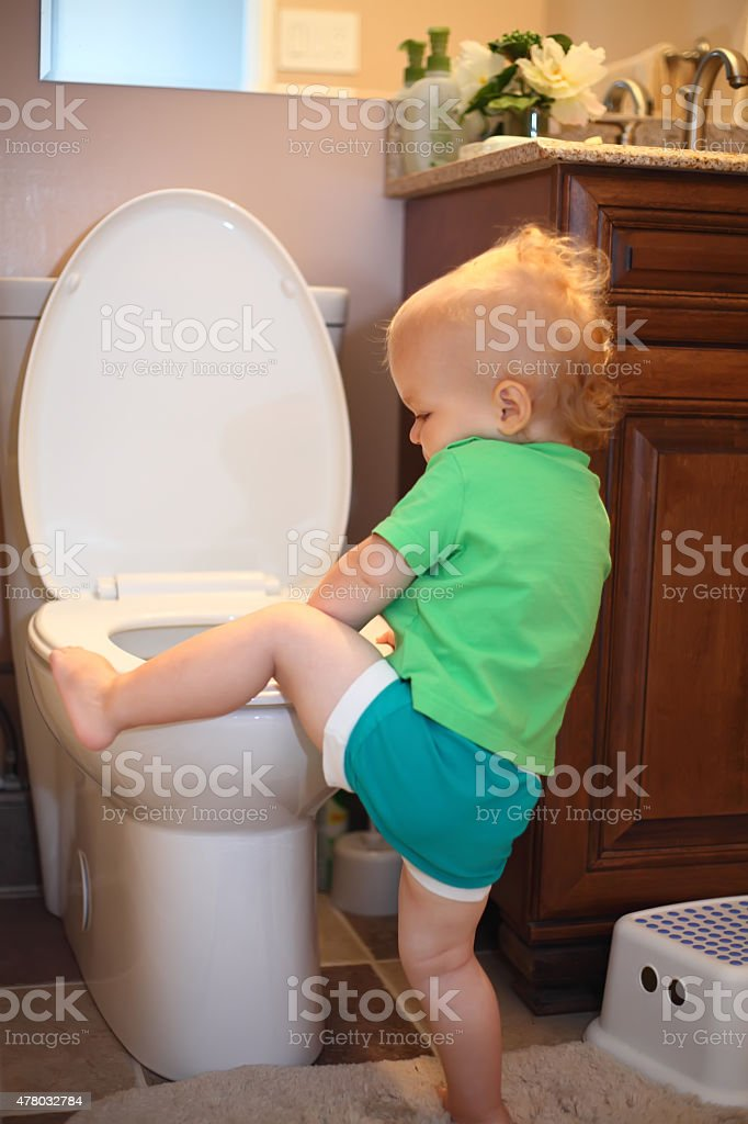 Baby trying to sit on a toilet stock photo