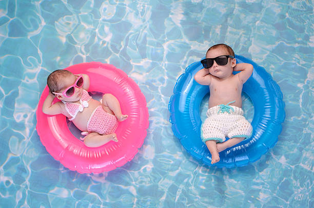 Baby Twin Boy and Girl Floating on Swim Rings Two month old twin baby sister and brother sleeping on tiny, inflatable, pink and blue swim rings. They are wearing crocheted swimsuits and sunglasses. cool attitude stock pictures, royalty-free photos & images