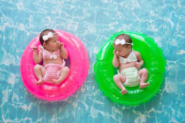 baby zwillinge schwimmend auf schwimmreifen - traum pools stock-fotos und bilder