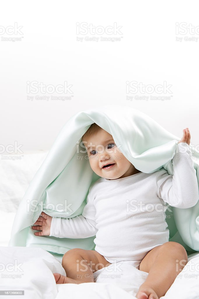 Baby Under a Blanket on the Bed stock photo