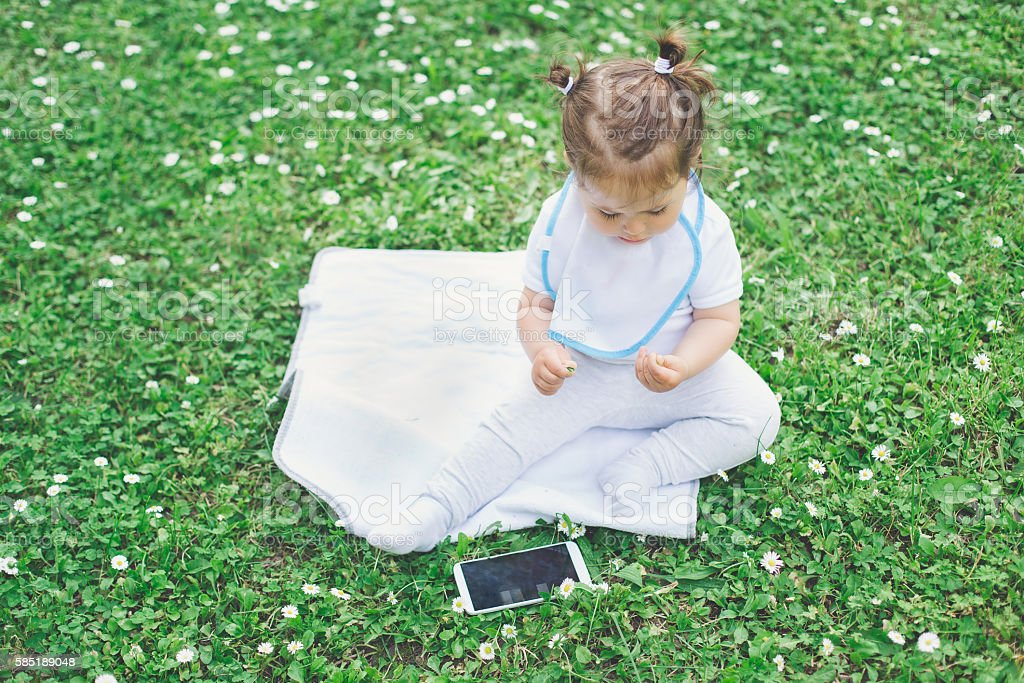 baby using phone while sitting on grass stock photo
