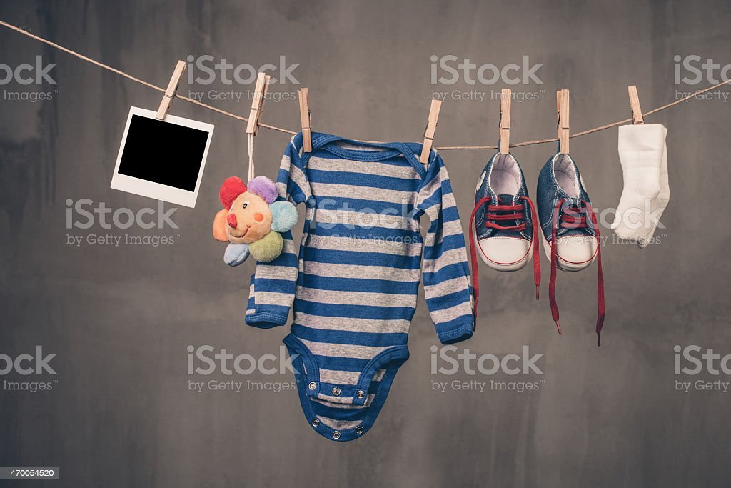 Baby vest shoes socks and photo hanging on a line by pegs stock photo