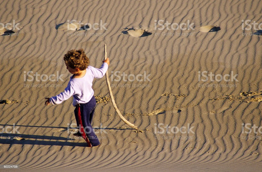 Baby walking in the sand stock photo