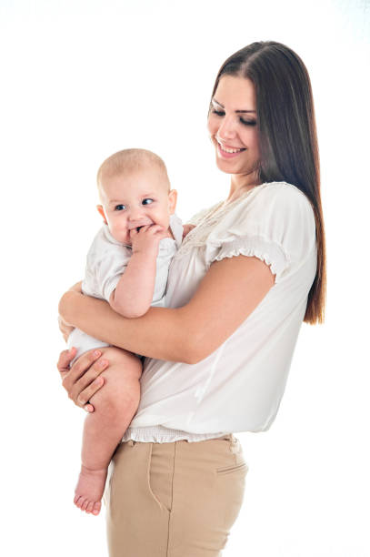 Baby was crying and biting your fingers, climb first teeth. Picture of happy mother with adorable infant stock photo