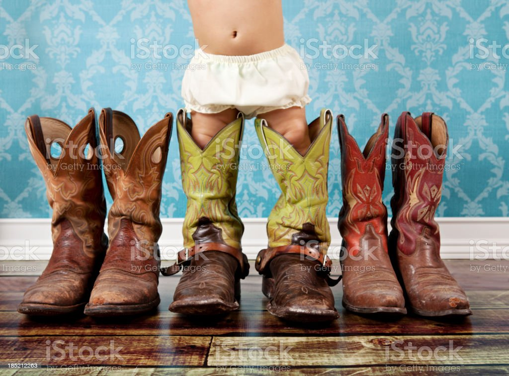 baby wearing her daddy cowboy boots stock photo