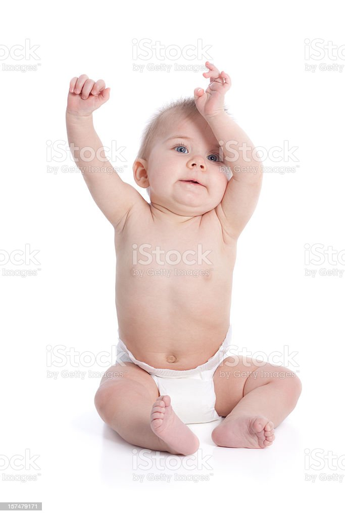 Baby wearing nappy sitting down with arms in the air stock photo