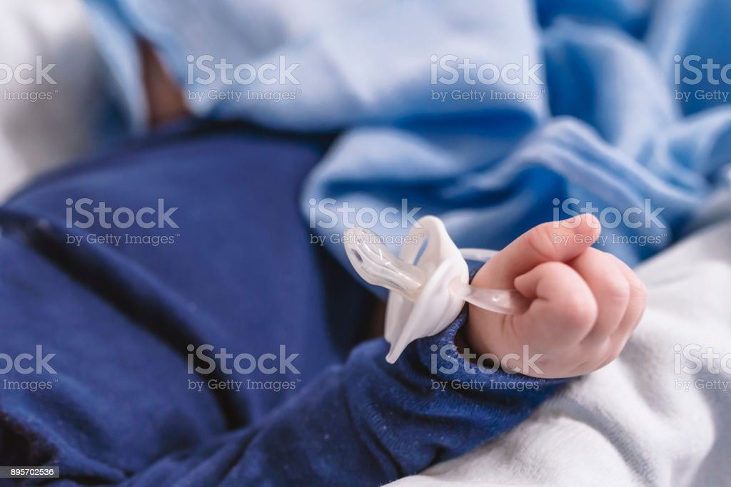 Baby with a nipple. Close up of baby hands with pacifier. stock photo