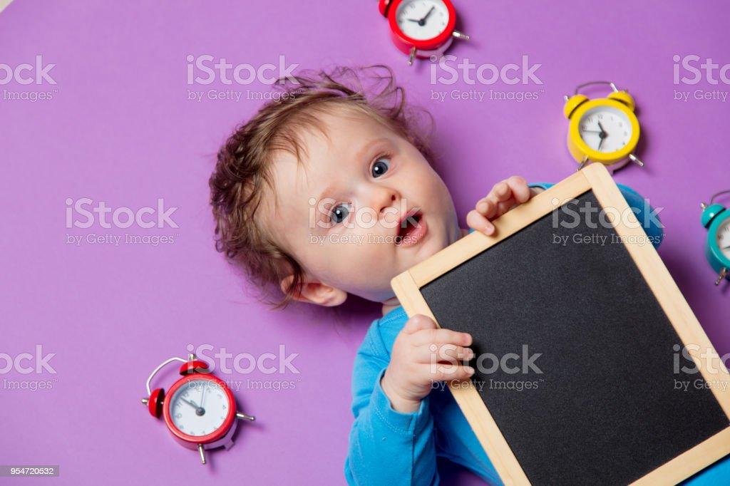 baby with alarm clock and blackboard stock photo