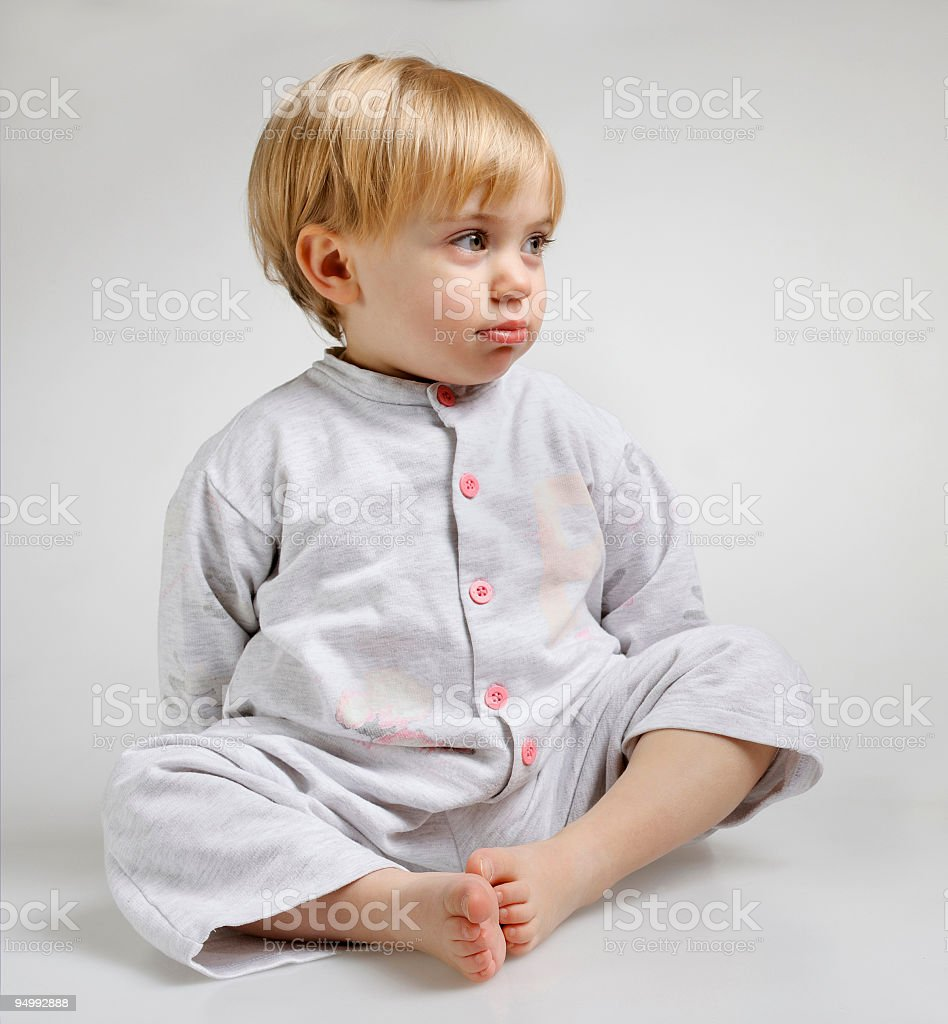 Baby with blond hair and blue eyes sitting in pyjamas stock photo