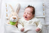 Adorable sleepy newborn baby with a toy bunny yawning in bed