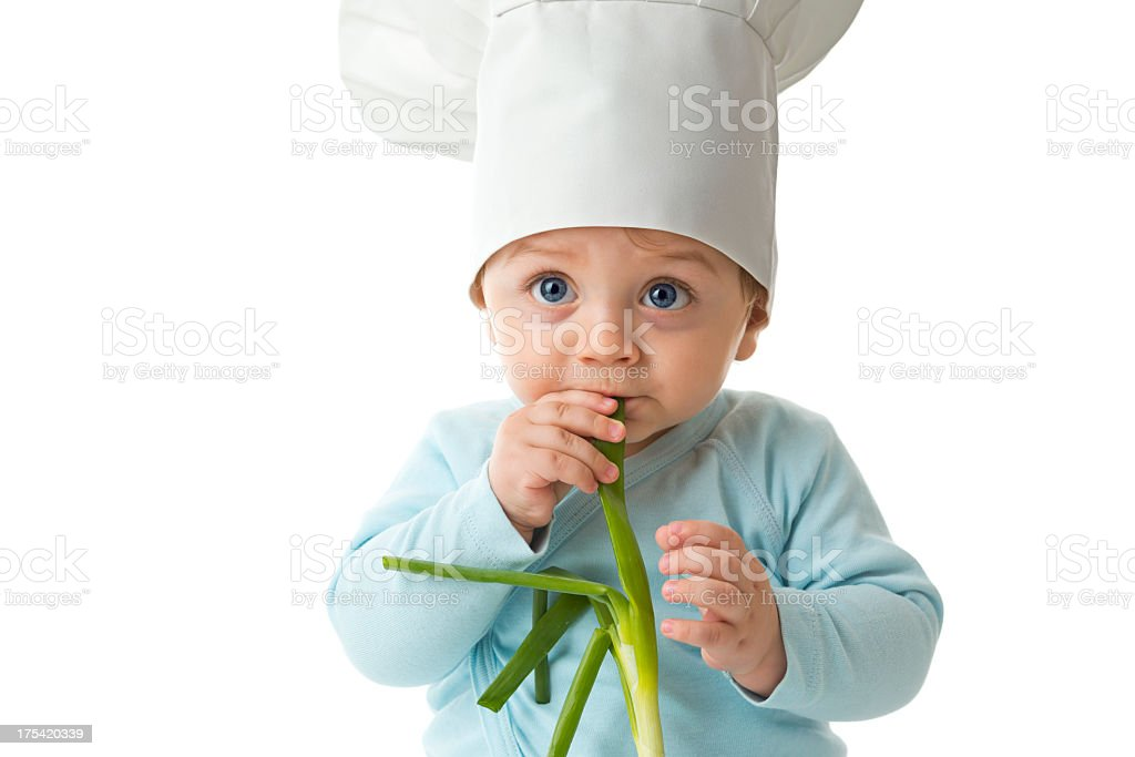 Baby with chef hat and fresh onion, biting it stock photo