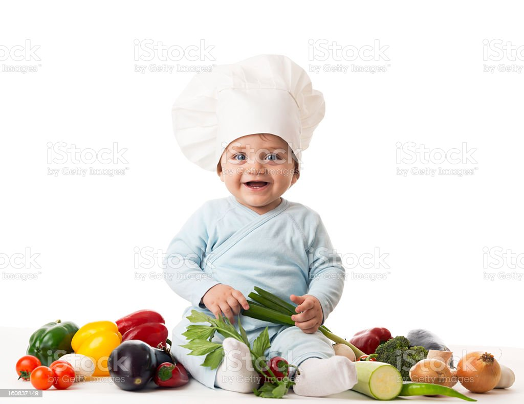 Baby with chef hat and fresh vegetables, smiling stock photo