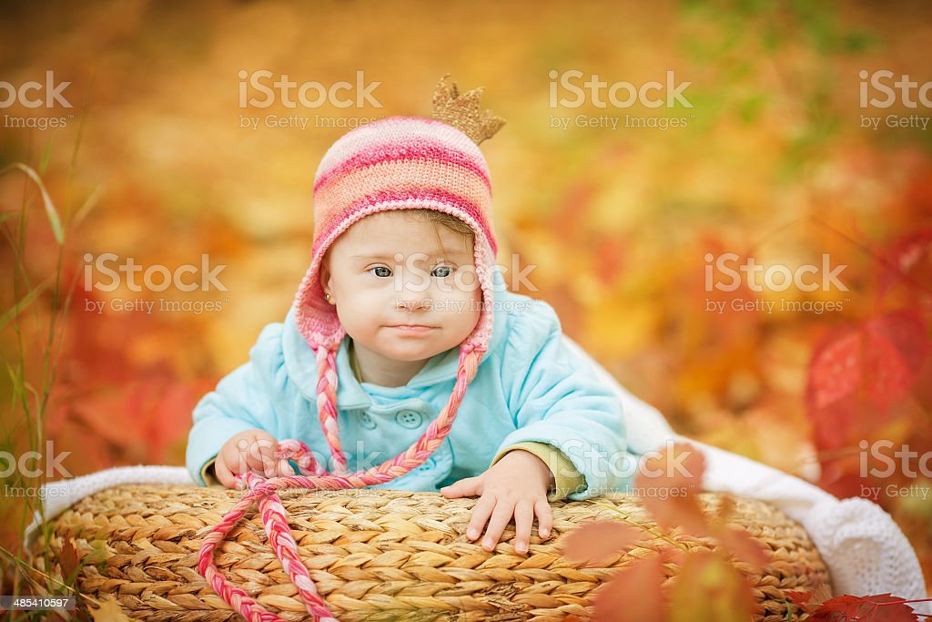 baby with Down syndrome is resting in autumn forest stock photo