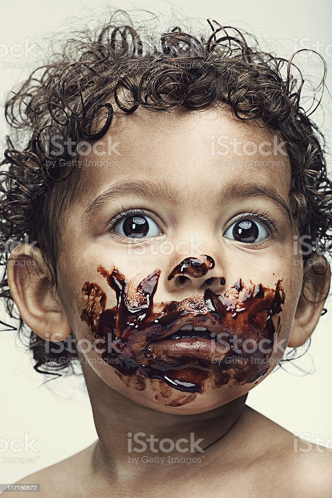 Baby with face covered in chocolate stock photo