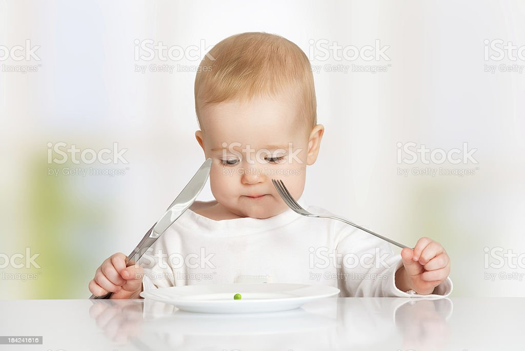 baby with fork and knife eating, stock photo