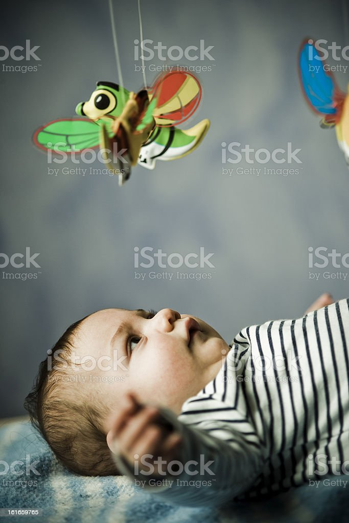 Baby, wearing striped shirt, lying down blanket and playing with...