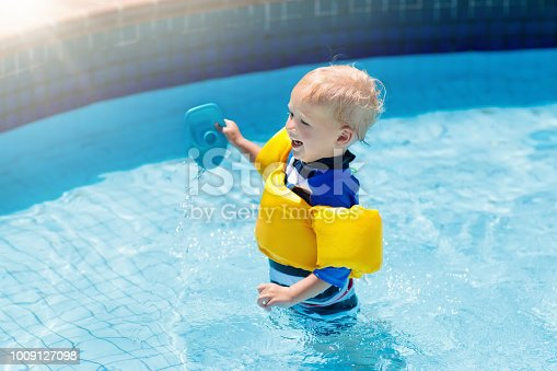 istock Baby with inflatable armbands in swimming pool. 1009127098