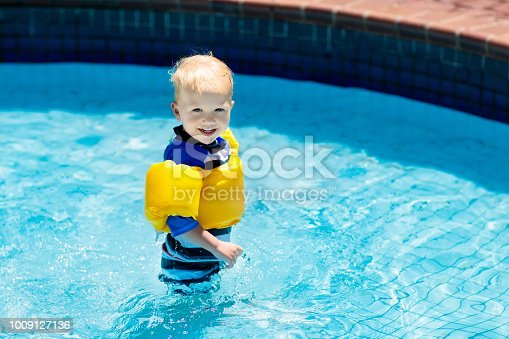 istock Baby with inflatable armbands in swimming pool. 1009127136
