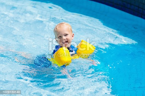 istock Baby with inflatable armbands in swimming pool. 1009130140