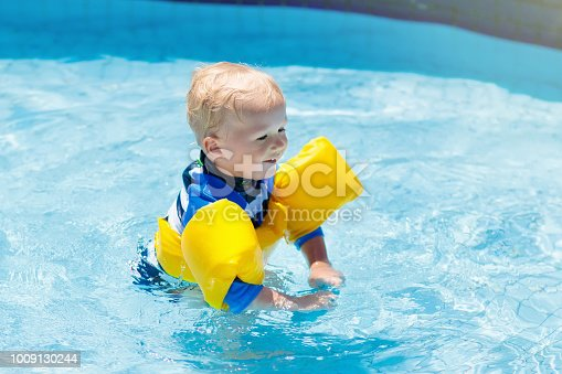 istock Baby with inflatable armbands in swimming pool. 1009130244