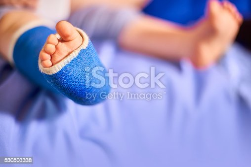 Baby in the hospital with it's leg in a blue cast to protect the broken bones.