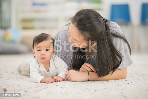 A baby boy and his mother are laying on the floor of a daycare center. The boy is looking at the camera curiously.