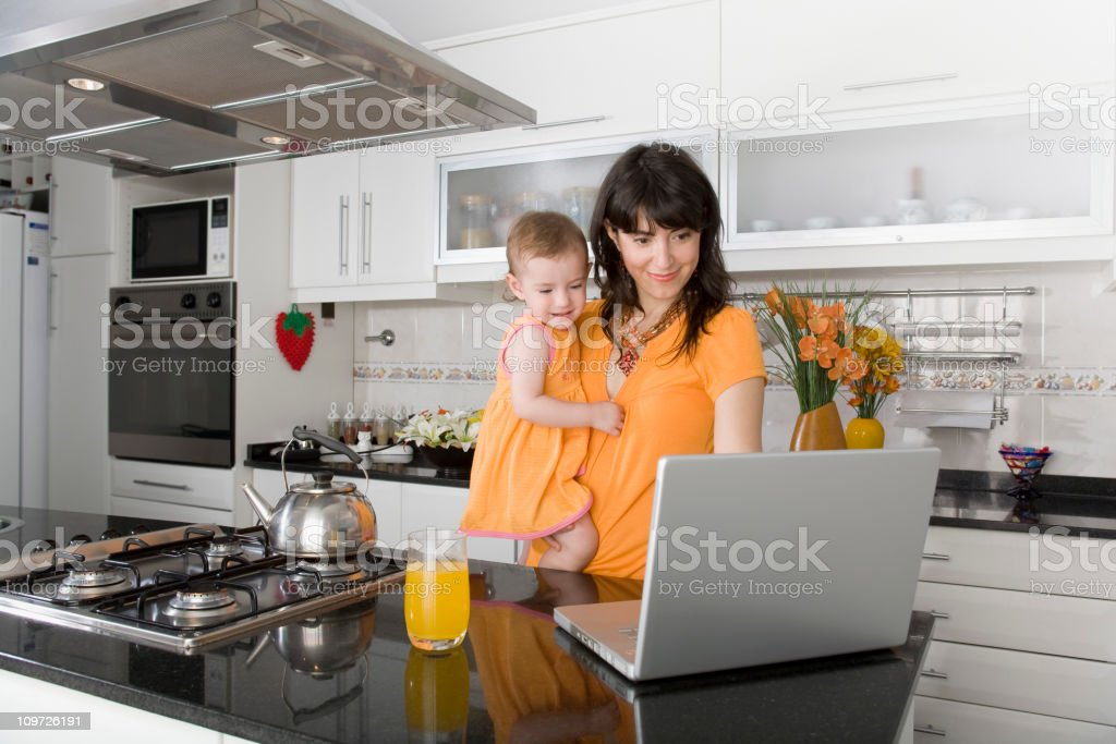 Baby with mother and laptop in the kitchen royalty-free stock photo