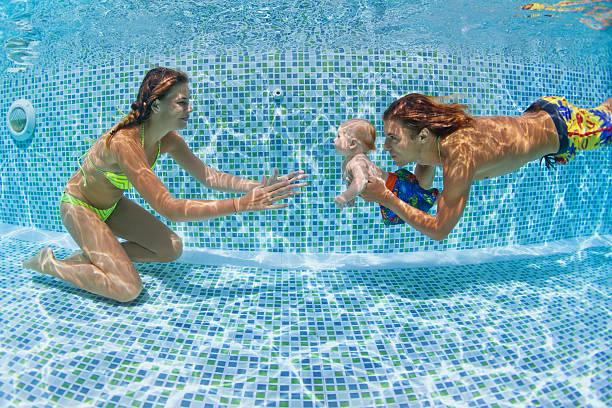 baby mit mutter, vater lernen, schwimmen, tauchen sie unter - lustige babybilder stock-fotos und bilder