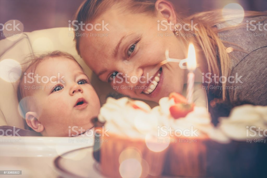 Baby with mother looking at birthday cake with candle  during celebration first birthday stock photo