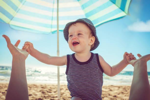 baby mit mutter am strand - outdoor sonnenschutz stock-fotos und bilder