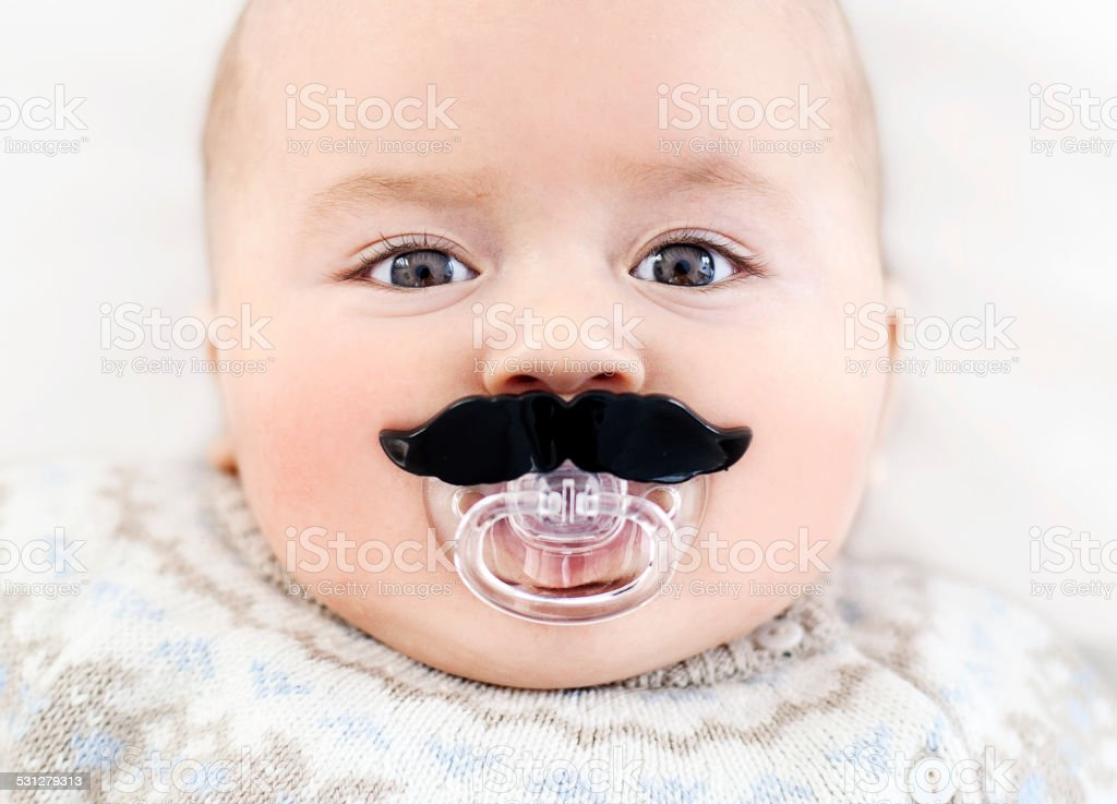 Baby with mustache pacifier stock photo