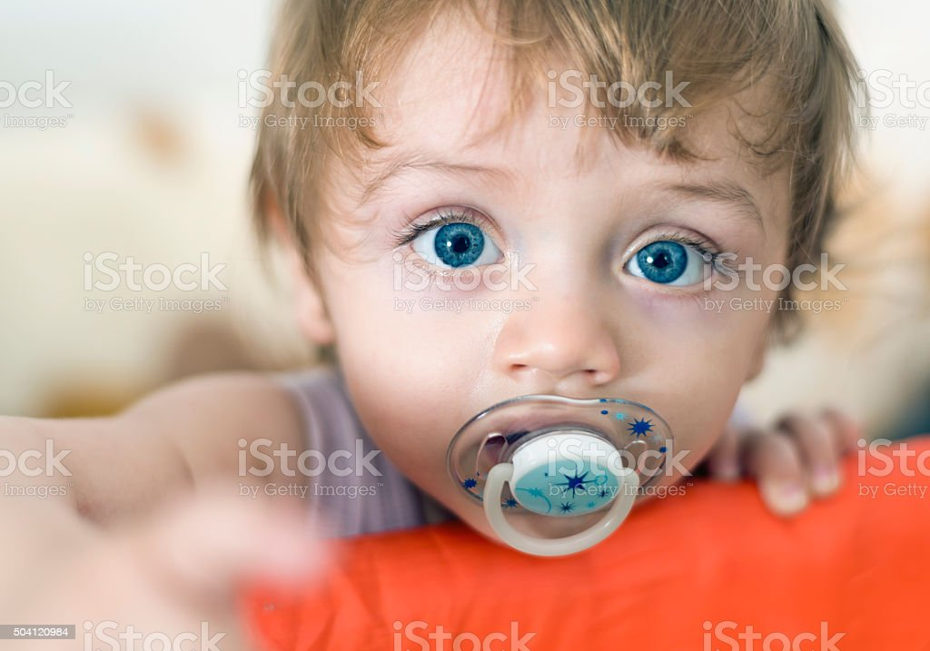 Baby with pacifier reaching to the camera stock photo