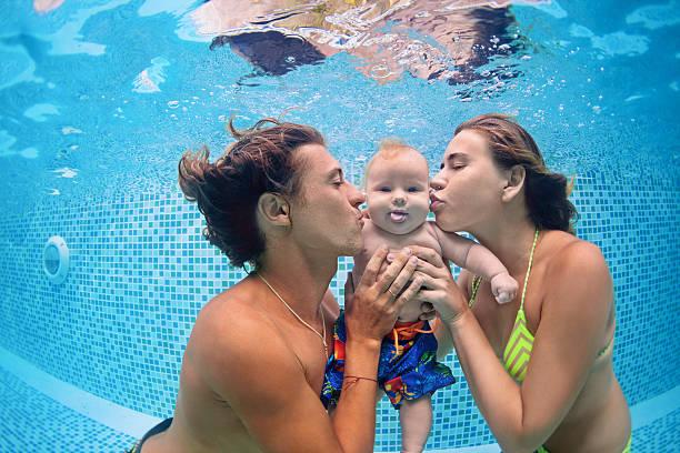 baby mit eltern lernen, schwimmen unter wasser im schwimmbad - lustige babybilder stock-fotos und bilder