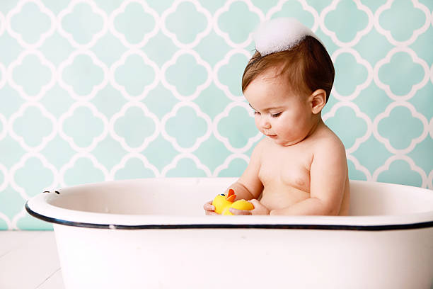 Baby with Rubber Ducky in Antique Bathtub stock photo