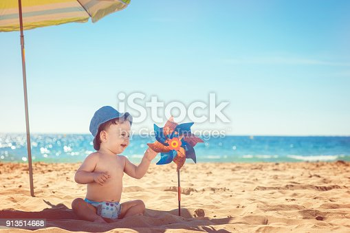 Cute baby with toy windmill on the beach