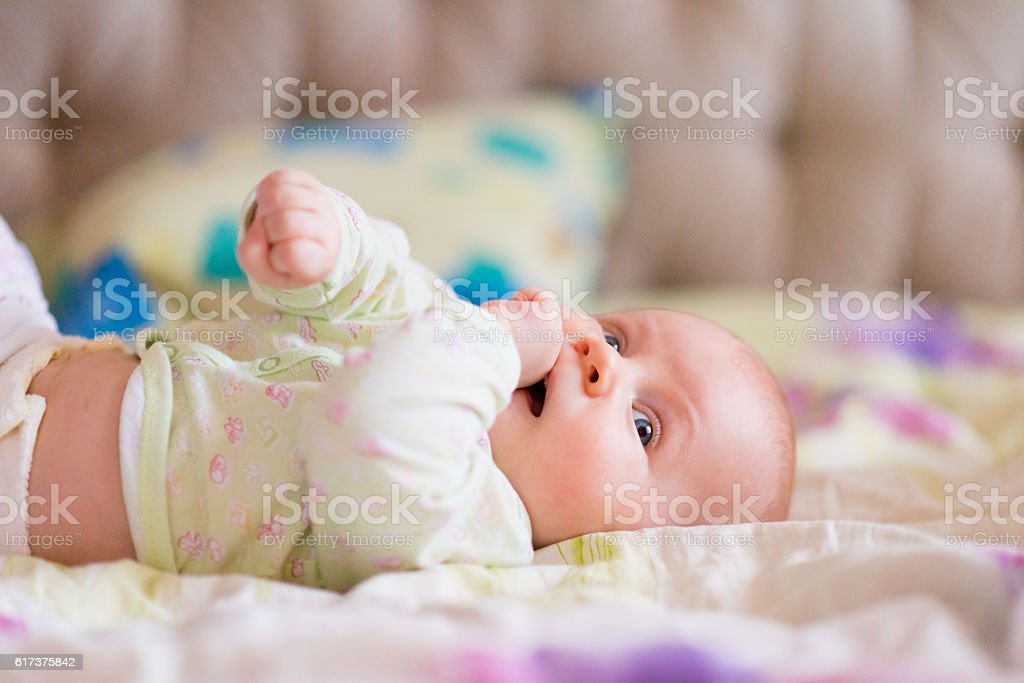 Baby woke up and laying on bed stock photo