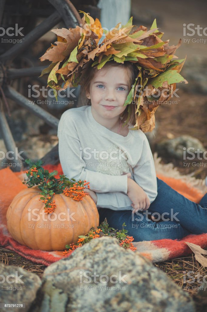 Baby young girl with blue eyes with brunnette plait hair and freckling cheek wearing white dress shirt and posing on red plaid close to pumpkin with autumn foliage wreathon head looking to camera stock photo