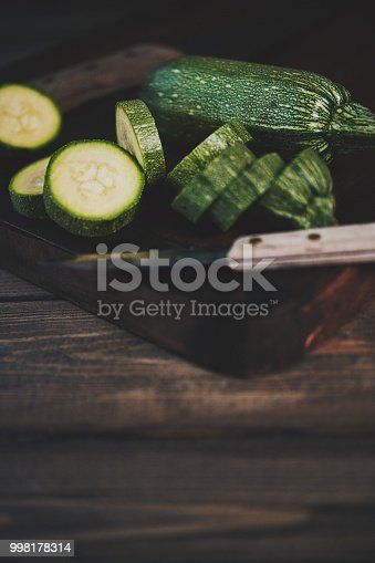 Baby zucchini on chopping board with knife