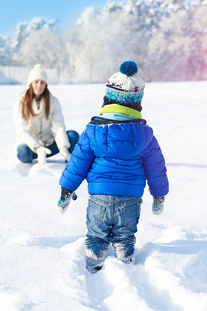 Babyboy son and mother are happy together, winter snowy day stock photo